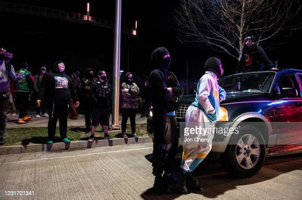 Group of protesters are illuminated by emergency lights from Louisville Metro Police Department vehicles after the Breonna Taylor memorial events on...