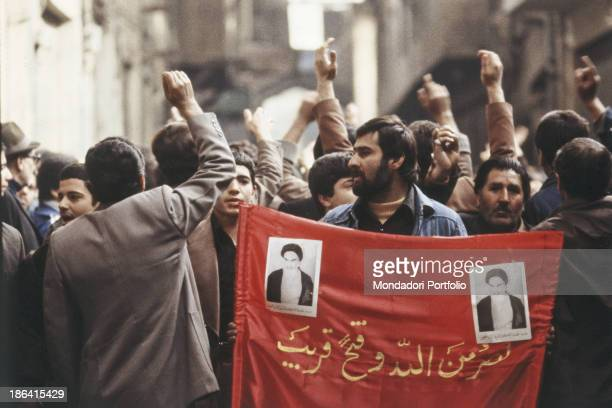 Group of protesters demonstrate during the iranian revolution with a banner of their leader Ruhollah Khomeyni. The Iranian population protests...