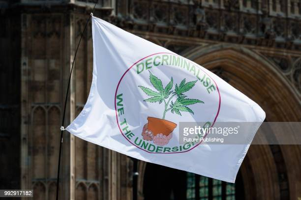 A group of protesters for the legalisation of medical marijuana in the United Kingdom wave flags during a rally outside Parliament in London on the...