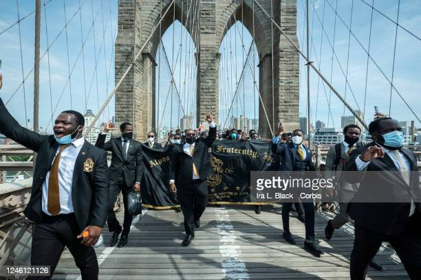 A group of protesters from the Alpha Phi Alpha fraternity holding up fists in the air and wearing suits walk with the arches of the Brooklyn Bridge...
