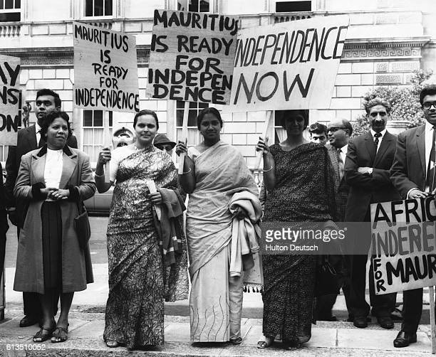 A group of protesters hold signs in support of Seewoosagur Ramgolam the Prime Minister of Mauritius who will speak out for Maurianian independence...