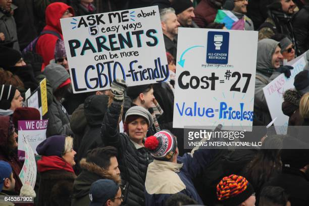 A group of protesters hold signs supporting transgender students February 25 2017 in Chicago during a protest against the Trump administration's new...