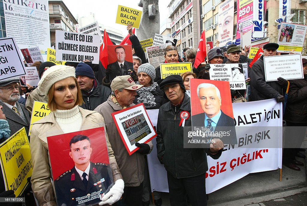 A group of protesters including the family members of more than 300 jailed military officers accused of plotting to overthrow Turkey's Islamic-rooted government, hold banners as they stage a demonstration for 'justice and fair trial' in Ankara on February 16, 2013. In September 2012 more than 300 retired and active military officers received prison sentences of up to 20 years after the court ruled that a military exercise dubbed 'Sledgehammer' in 2003 was an undercover coup plot. Pro-government circles have praised the investigations as a step toward democracy but critics have branded them witch-hunts aimed at stifling opposition.