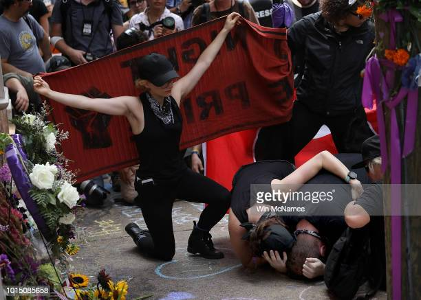 A group of protesters known as 'Antifa' or antifascists mourn at the site of a makeshift memorial where Heather Heyer was killed last year August 11...