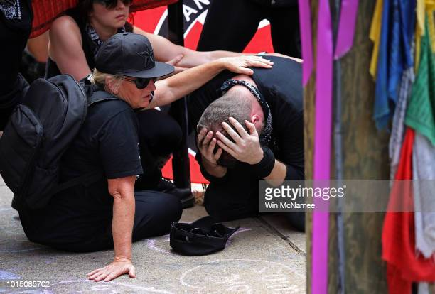 A group of protesters known as Antifa or antifascists mourn at the site of a makeshift memorial where Heather Heyer was killed last year August 11...