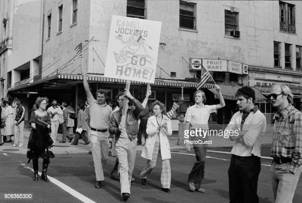 A group of protesters several with American flags and one with a sign cross a street during a demonstration about the Iran Hostage Crisis Washington...