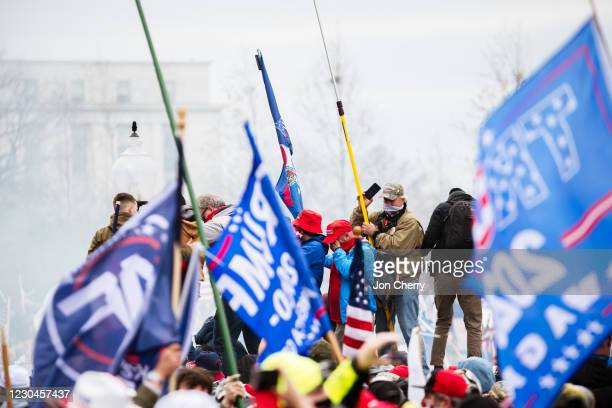 Group of protesters suffer the effects of teargas dispersed by police after storming the grounds of the Capitol Building on January 6, 2021 in...