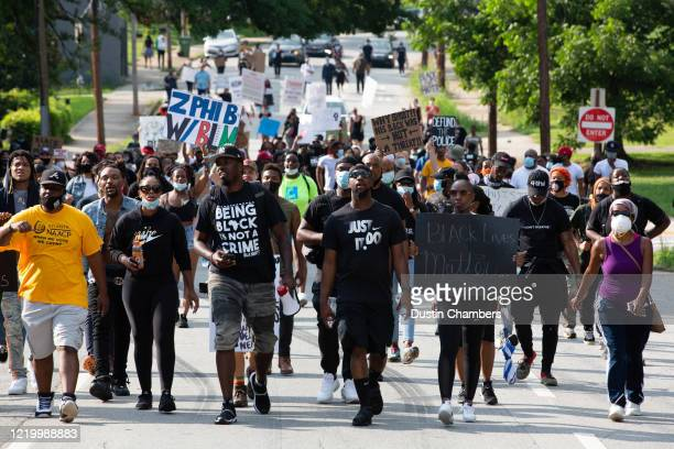 A group of protesters walks on a road after a night of protests during which a Wendy's restaurant was set ablaze overnight on June 14 2020 in Atlanta...
