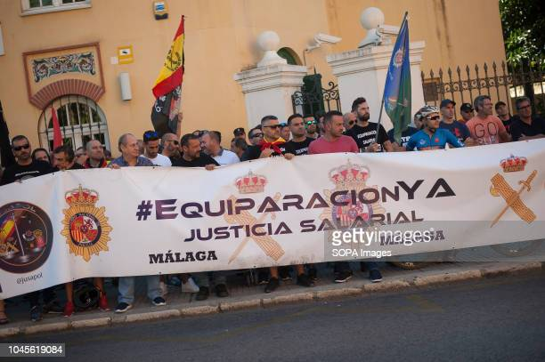 A group of protestors hold a large banner demanding equal salaries as they take part in a protest in support of national police officers and civil...