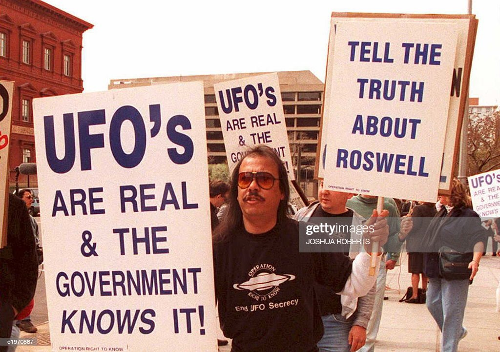 A group of protestors march in front of the General Accounting Office (GAO) 29 March to raise awarness about an examination being conducted by the GAO for documents about a weather balloon crash at Roswell, N.M. in 1947. The protestors believe the balloon was a crashed UFO.