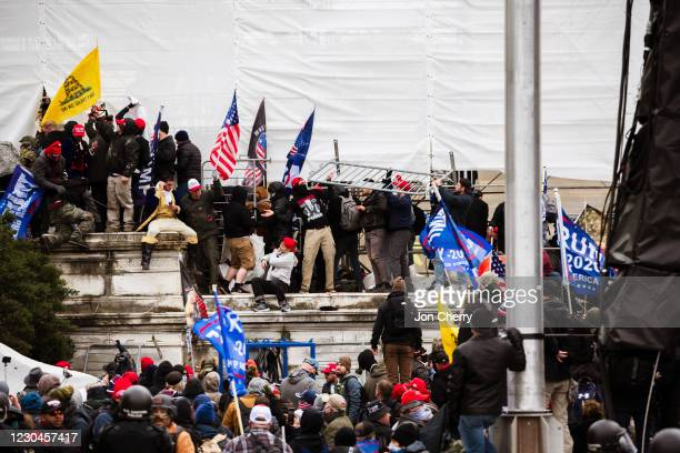 Group of pro-Trump protesters climb the walls of the Capitol Building after storming the West lawn on January 6, 2021 in Washington, DC. A pro-Trump...