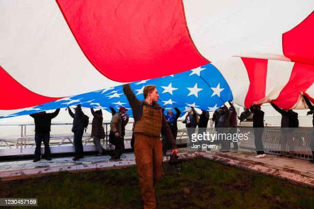 Group of pro-Trump protesters raise a giant America Flag on the West grounds of the Capitol Building on January 6, 2021 in Washington, DC. A...