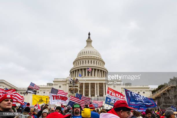 Group of pro-Trump protesters raise signs and flags on the grounds of the Capitol Building on January 6, 2021 in Washington, DC. A pro-Trump mob...