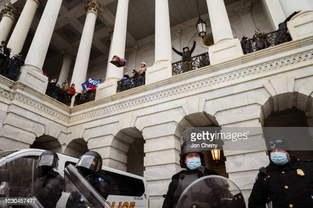 Group of pro-Trump protesters wave flags from a platform above a group of Capitol Police after storming the Capitol Building on January 6, 2021 in...