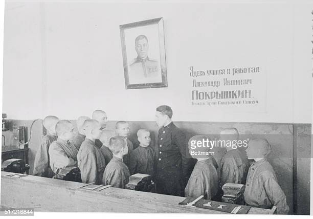 A group of pupils and their teacher stand beneath a picture of Alexandr Pokryshkin Soviet ace pilot who was a student at this school before its...