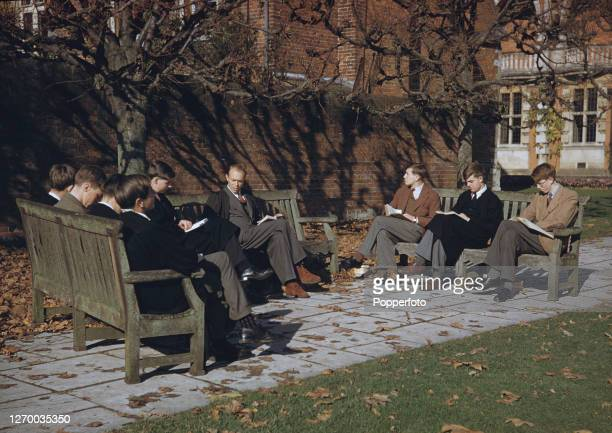 Group of pupils from Winchester College public boarding school sit on benches with a teacher during a classics lesson conducted outdoors in the...
