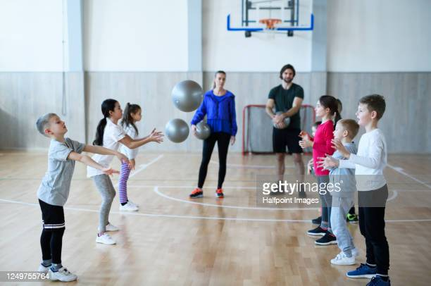 group of pupils with teachers exercising indoors in gym class. - physical education stock pictures, royalty-free photos & images