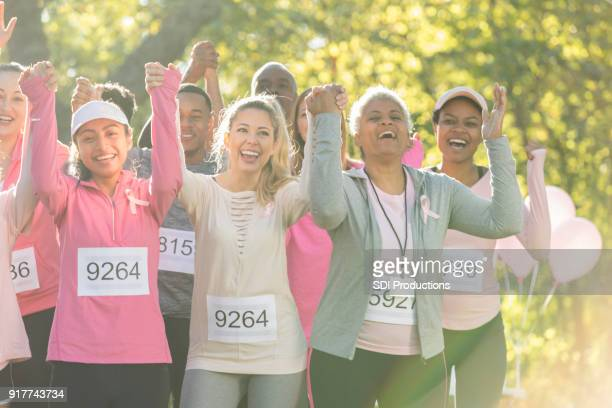 group of race for cure participants holding hands for camera - charity benefit stock photos and pictures