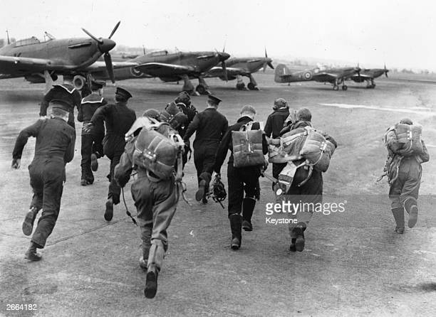 A group of RAF pilots and sailors scramble for their planes during an alert at a training centre for the Fleet Air Arm