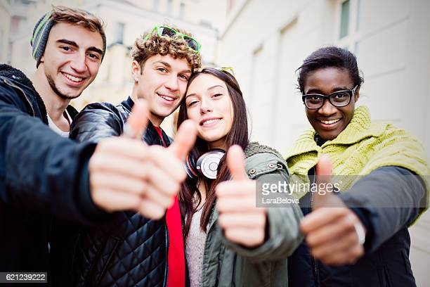Group of real multi ethnic friends making thumb up