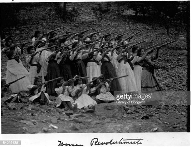 A group of rebel women and girls wearing traditional dress practice their shooting skills for the Mexican Revolution in 1911