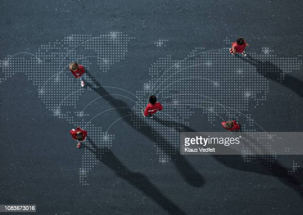 group of red dressed children walking and standing on world map - global village stock pictures, royalty-free photos & images