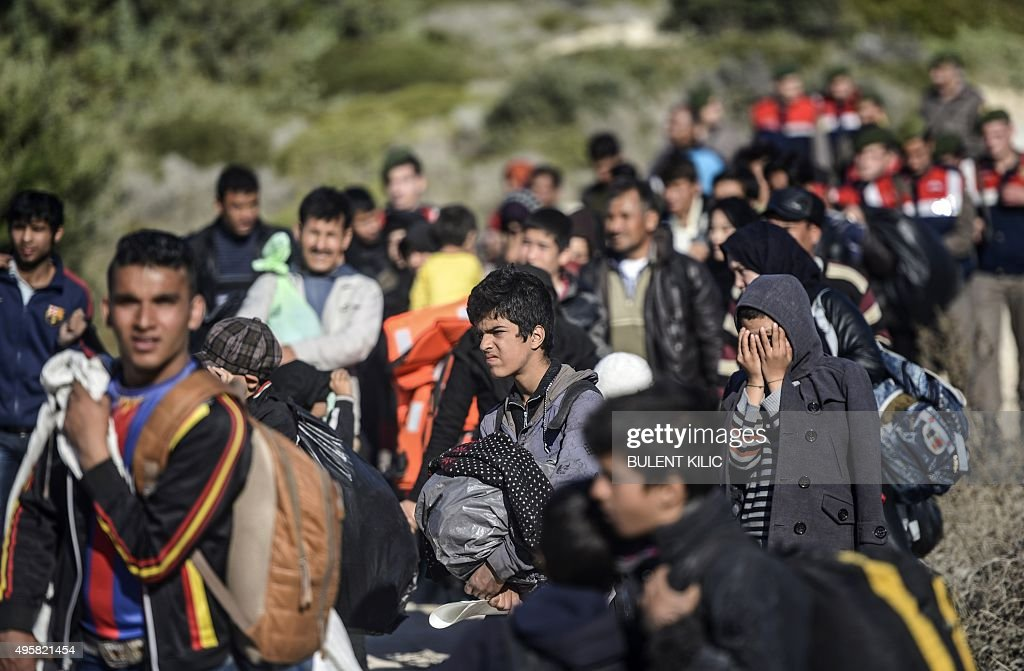 A group of refugees, led by Turkish police, are escorted to buses in place of sailing to the Greek island of Chios via raft, at a beach in the western Turkish coastal town of Cesme, in Izmir province, on November 5, 2015. Up to 600,000 migrants and refugees are expected to cross from Turkey to Greece and onwards over the next four months, the UN said Novewmber 5, with the flow set to persist through the winter. The UN refugee agency (UNHCR) released the figures in a planning document that highlights the additional needs of migrants moving toward or within Europe as the weather turns cold.