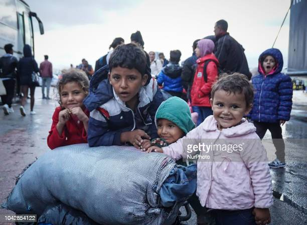 A group of refugees posing a photograph following they disembark at the Port of Piraeus 29 September 2018 Thousand migrants and refugees are...
