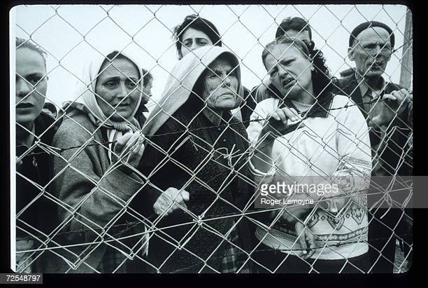 A group of refugees stands behind a fence April 1 1999 in Macedonia Thousands of Kosovar Albanians fled the violence in Serbia and arrived at Blace a...