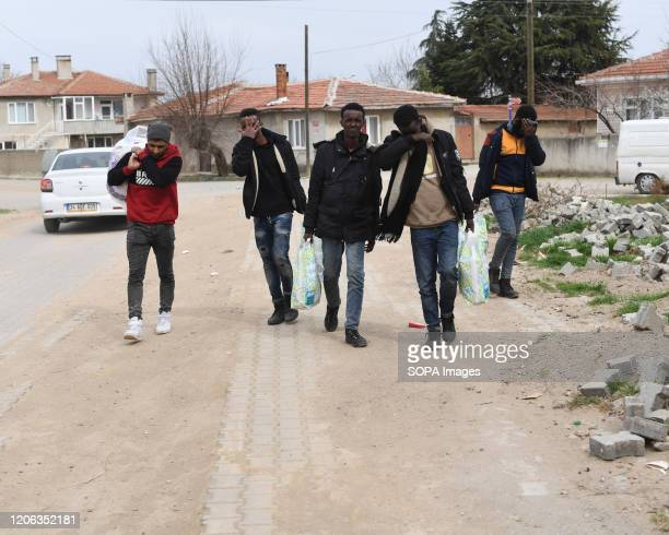 Group of refugees walking on the road hide their faces. The humanitarian crisis in Edrine, Turkey on the border with Greece is currently at a...