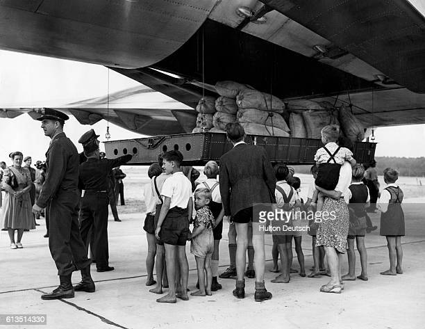 A group of refugees watches in anticipation as a platform teaming with flour sacks descends from the cargo hold of the mammoth Douglas C47...