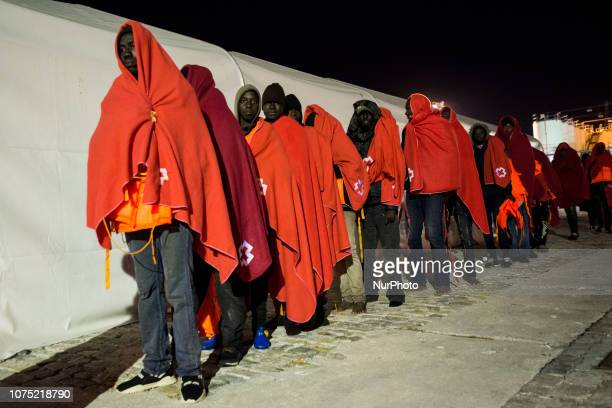 A group of rescued is queuing at the entrance of the Care unit where the Red Cross staffs will attend them on 22 December 2018 in Malaga Spain 120...