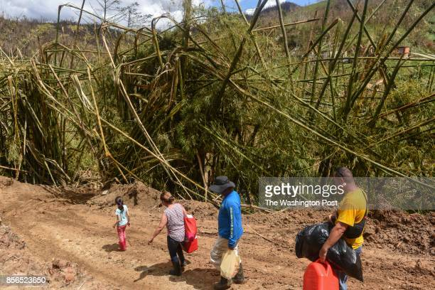 A group of residents walk down a road that is impassable now to traffic in the hard hit mountain areas around Caonillas Puerto Rico on September 29...