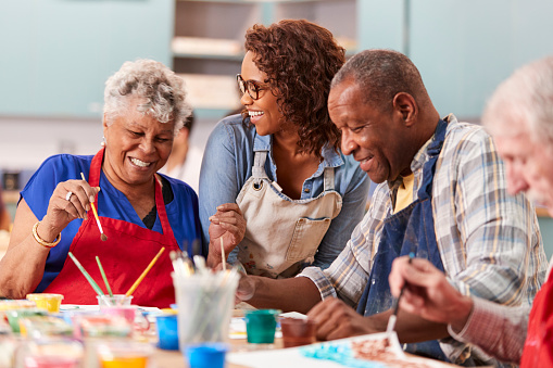 Group Of Retired Seniors Attending Art Class In Community Centre With Teacher 1145048249