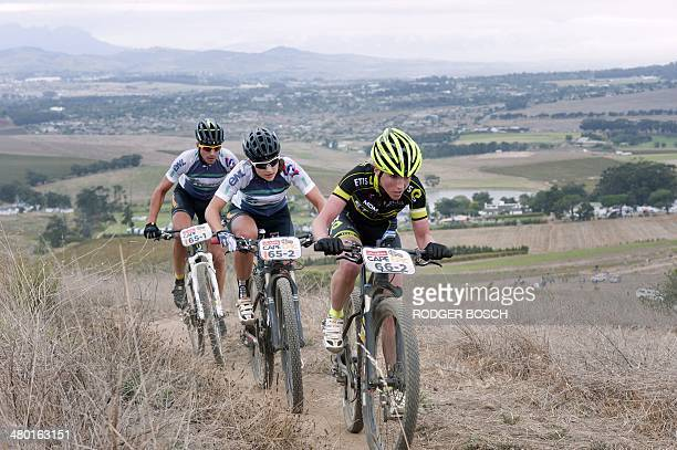 A group of riders compete during the prologue stage of the 2014 Cape Epic mountain bike race at Meerendal wine farm on March 23 in Durbanville about...