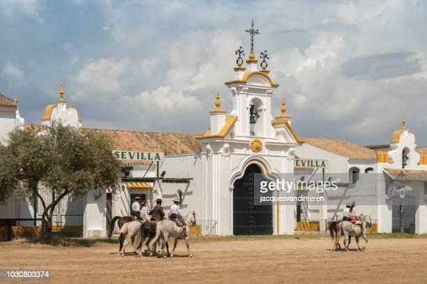 group of riders pass the house of the hermandad of seville in el rocio, spain, during the romeria del rocio. - pentecostes imagens e fotografias de stock
