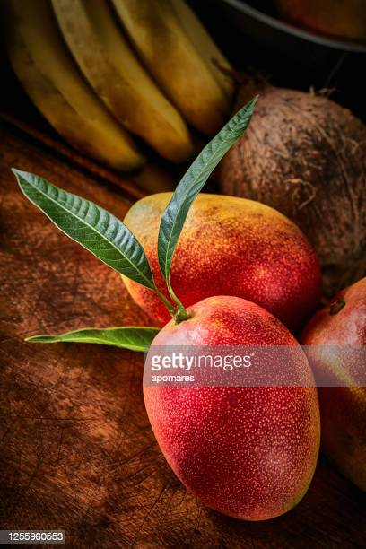素朴なキッチンのテーブルの上に熟したトロピカルフルーツのグループ - 熟した ストックフォトと画像