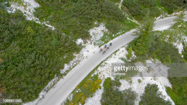 groep van fietsers van de weg rijden op mooie bergweg omgeven door bos - wielrennen stockfoto's en -beelden