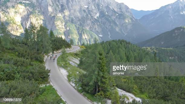 groep van fietsers van de weg rijden op mooie bergweg omringd door bomen en bergen - wielrennen stockfoto's en -beelden
