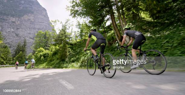 group of road cyclists riding on beautiful mountain road surrounded by trees - road cycling stock pictures, royalty-free photos & images