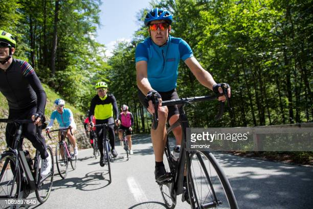 group of road cyclists riding road bikes on mountain road - road cycling stock pictures, royalty-free photos & images