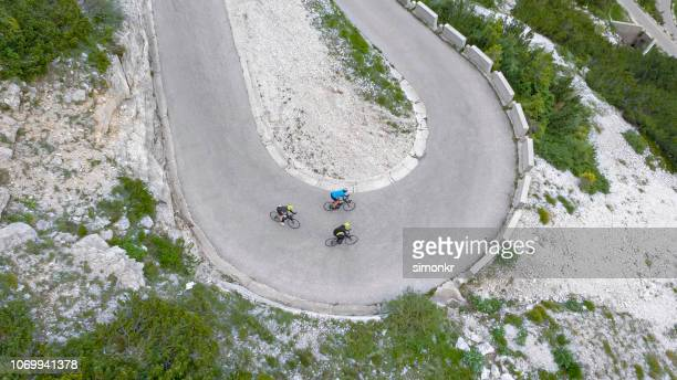 group of road cyclists riding up mountain road - road cycling stock pictures, royalty-free photos & images