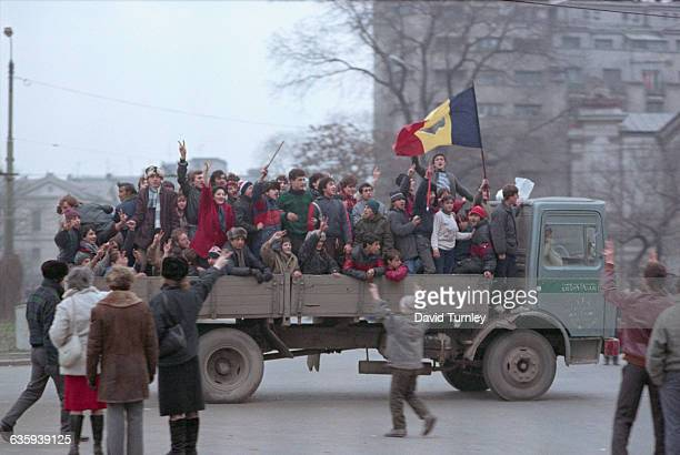 A group of Romanians ride in a truck rejoicing in the overthrow of Nicolae Ceausescu and wave the Romanian flag with the Communist device cut out of...