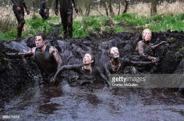 Group of runners jump in to a mud hole as competitors take part in the annual McVities Mud Madness 8km cross country run on April 9, 2017 in...