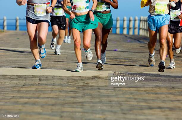 group of runners on paved road - road race stock pictures, royalty-free photos & images