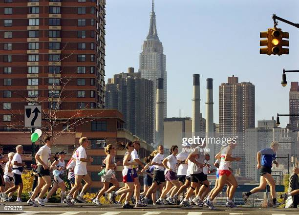 Group of runners passes through Queens during the 32nd New York City Marathon November 4, 2001. The Empire State Building is seen in the background.