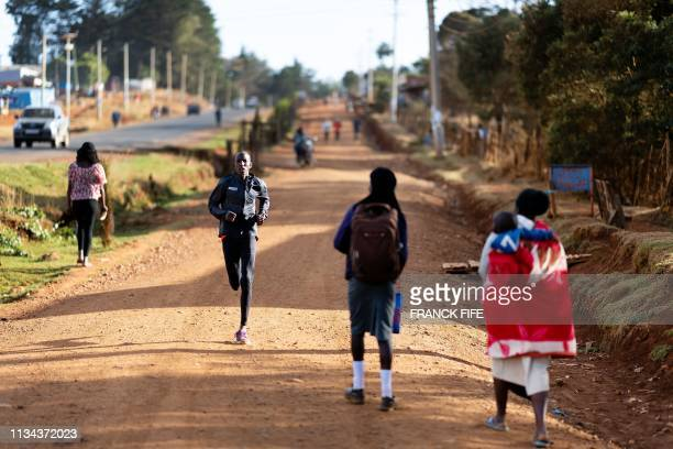 A group of runners takes part a training session on March 13 2019 in Iten Kenya As dawn breaks high in Kenya's Rift Valley car headlights pick out...