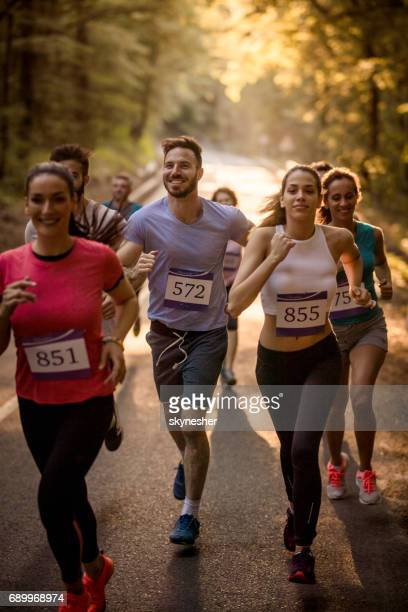 Group of runners taking part in a marathon race through the forest.