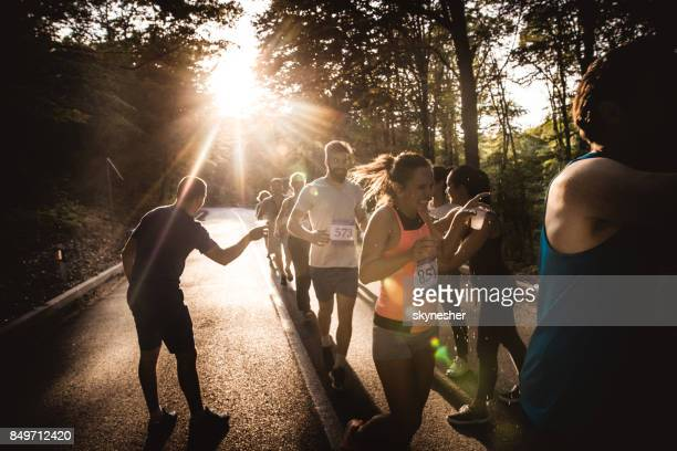 Group of runners taking refreshment from volunteers during a marathon.