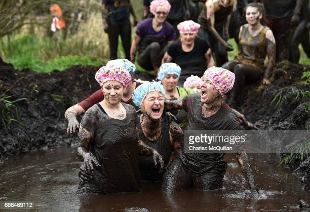 Group of runners wearing shower caps make their way through a mud hole as competitors take part in the annual McVities Mud Madness 8km cross country...
